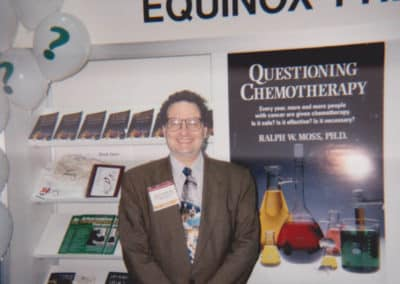 Ralph W. Moss, Phd stands in front of a large display of his books and banners at the American Library Association meeting in New Orleans 1996